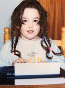 Katie Lowe as a child at a typewriter